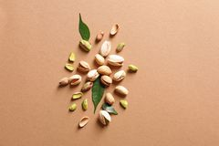 Composition with organic pistachio nuts on color background. Flat lay. Space for text stock image