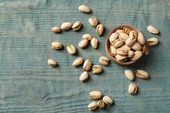 Composition with organic pistachio nuts on wooden table, flat lay. Space for text royalty free stock photos