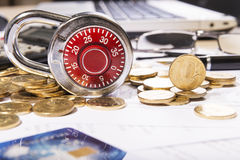 Composition of the padlock on coins Stock Images