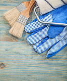 Composition of paint roller brushes safety gloves on wood board Stock Images