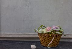 Composition of painted Easter eggs on dark stone table and vintage white wall background royalty free stock images
