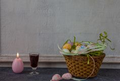 Composition of painted Easter eggs on dark stone table and vintage white wall background royalty free stock image