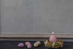 Composition of painted Easter eggs on dark stone table and vintage white wall background stock image