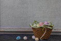 Composition of painted Easter eggs on dark stone table and vintage white wall background royalty free stock photo