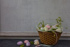Composition of painted Easter eggs on dark stone table and vintage white wall background stock images