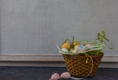 Composition of painted Easter eggs on dark stone table and vintage white wall background stock photo
