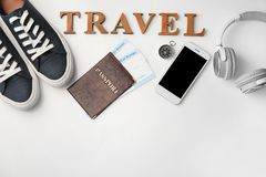 Composition with passport, immigration bureau cards, smartphone and word \'Travel\' on white background stock photography