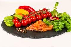 Composition of pasta fresh tomato, pepper, fish, radish on black stone board, white background. Composition of pasta fresh tomato, pepper, fish, radish on black royalty free stock photos