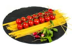 Composition of pasta fresh tomato, pepper, radish on black stone board, white background. stock image