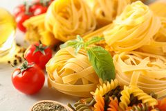Composition with pasta, tomatoes, spices and olive oil on white background royalty free stock image