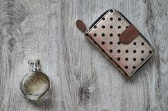 Perfume, purse. Composition, perfume in a glass bottle and a purse on a wooden background stock photo