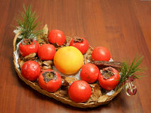 Composition of persimmon, grapefruit and pine cone in the dish o Royalty Free Stock Images