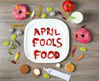 Composition with phrase. `April fools food` and treats on wooden background Royalty Free Stock Photos