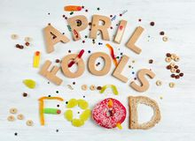 Composition with phrase. `April fools food`, doughnut and jelly candies on wooden background Royalty Free Stock Photography