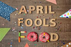 Composition with phrase. `April fools food`, doughnuts and jelly candies on wooden background Royalty Free Stock Image