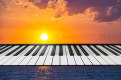 Composition of piano keyboard on marine background with a setting sun. Concept of music, nature, creation, unity of music and nature royalty free stock photos