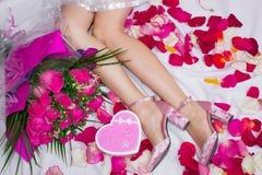 Composition, pieds femelles en sandales sur une feuille avec des pétales de rose, et un bouquet des roses et d'une boîte sous for photographie stock libre de droits