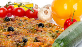 Composition with a pizza and some ingredients. Composition with a pizza, oil and fresh vegetables Royalty Free Stock Photos