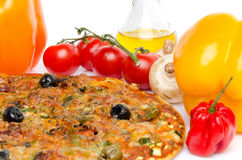 Composition with a pizza and some ingredients. Composition with a pizza, oil and fresh vegetables Stock Images