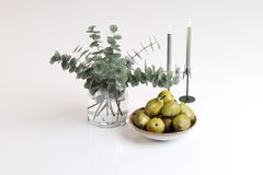 Plant of a vase, candles and a pear in a plate. Composition of a plant of a vase, candles and a pear in a plate Stock Image