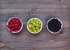Composition from plates with raspberries, grapes, currants. Composition of plates with raspberries, grapes, currants on dark wooden boards royalty free stock photos
