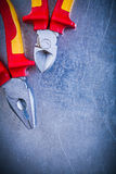 Composition of pliers wire-cutter on metallic background electri Royalty Free Stock Photos