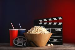 Composition with popcorn, cinema clapperboard and film reel on tabl. E against color background stock photography