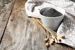 Composition with poppy seeds. On wooden table stock image