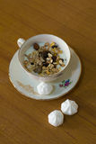 Composition of a porcelain cup and saucer filled with yogurt and muesli and three white sweets Royalty Free Stock Photography