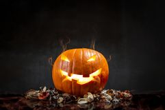 Composition of pumpkin on black background with glowing smoke. H royalty free stock photos