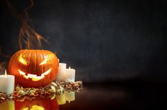 Composition of pumpkin and candles on black background royalty free stock image