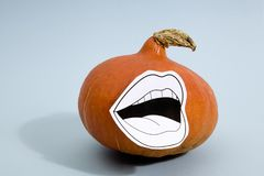 Pumpkin mouth. Composition of a pumpkin wearing a paper drawn mouth on a pop vibrant blue background Royalty Free Stock Photo