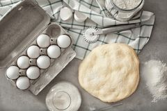 Composition with raw flaky dough and carton. Of eggs on table Royalty Free Stock Images