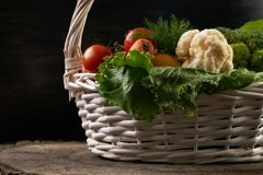 Composition with raw fresh vegetables and fruits in wicker basket stock image