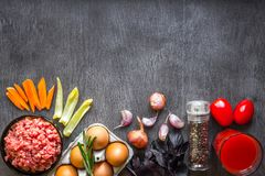Composition of raw meat with vegetables and spice on wooden background. Top view. Copy space. Still life. Flat lay Stock Images
