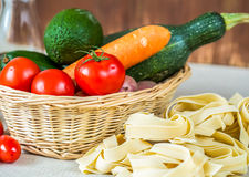 Composition with raw pasta,vegetables and olive oil Royalty Free Stock Images