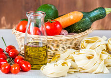 Composition with raw pasta,vegetables and olive oil Stock Images