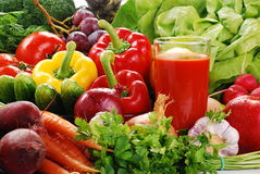 Composition with raw vegetables. Freshly washed vegetables with visible drops of water and glass of vegetable juice Royalty Free Stock Images