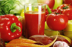 Composition with raw vegetables. Freshly washed vegetables with visible drops of water and glass of vegetable juice Stock Image