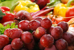 Composition with raw vegetables and grapes. Freshly washed grapes and vegetables with visible drops of water Royalty Free Stock Images