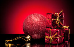Composition of red ball and small gift boxes. Composition of red christmas ball and small gift boxes on gradient background Royalty Free Stock Photo