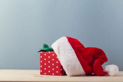 Composed present and Santa hat. Composition of red box in polka dots arranged with Santa hat on blue background stock photos