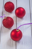 Composition of red christmas baubles on white painted boards Royalty Free Stock Photography