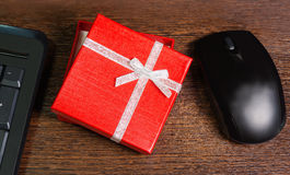 Composition with red gift box,  mouse and keyboard Stock Photography