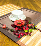 Composition of red, green home decorating flowers and leaves and a white cup and plate on a table Royalty Free Stock Image