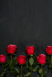 Composition of red roses on dark grey background. Romantic shabby chic decor. Top view. Love Concept. Valentines day. Roses with Gift box and pink ribbon on Stock Photo