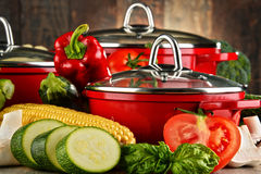 Composition with red steel pots and variety of fresh vegetables Stock Photos