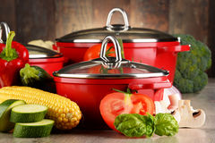 Composition with red steel pots and variety of fresh vegetables Royalty Free Stock Photos