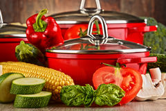 Composition with red steel pots and variety of fresh vegetables Stock Photography