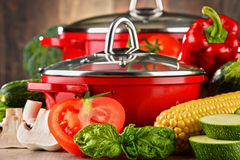 Composition with red steel pots and variety of fresh vegetables Royalty Free Stock Images
